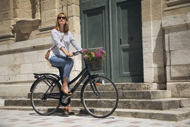 Femme à vélo, la trentaine avec ballerines Petites-Dalles de chez maison Castille en cuir lisse camel avec noeud plat noir