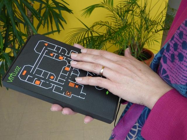 Photo de Virtuoz mini. De la dimension d'un tablette avec un plan en relief dessus, le fond est noir et les contours des murs et les symbols en couleur.